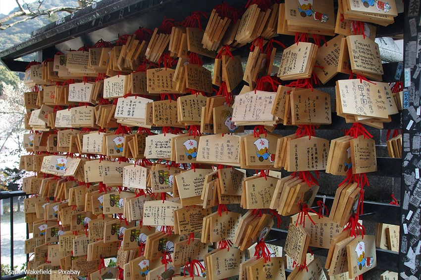 Holzplättchen mit Wünschen an einem Schrein