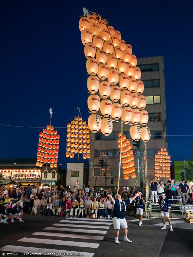 Teilnehmer des Akita Kanto Festivals balanciert Stab mit Papierlaternen