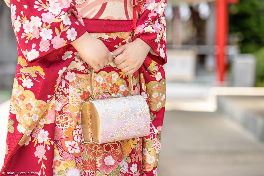 Frau im roten Kimono mit Kirschblüten und Handtäschchen