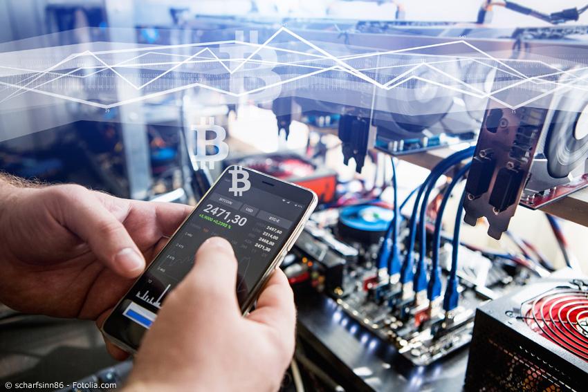Mobiltelefon mit Kursübersicht, im Hintergrund Bitcoin Miner