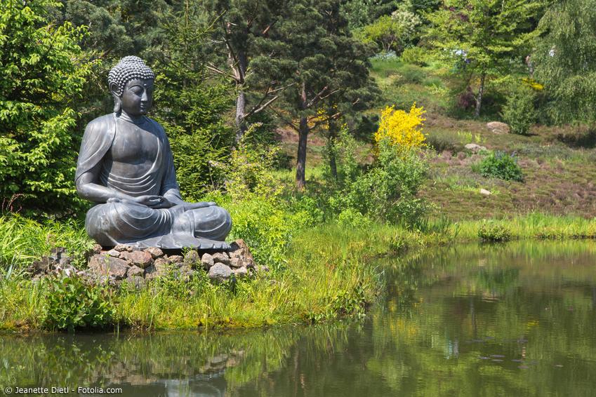 Buddhafigur auf Steinbett an einem Teich im Japangarten