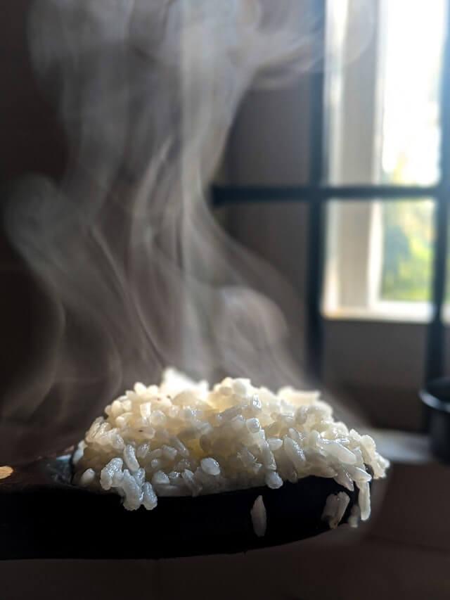 Löffel mit dampfendem Reis