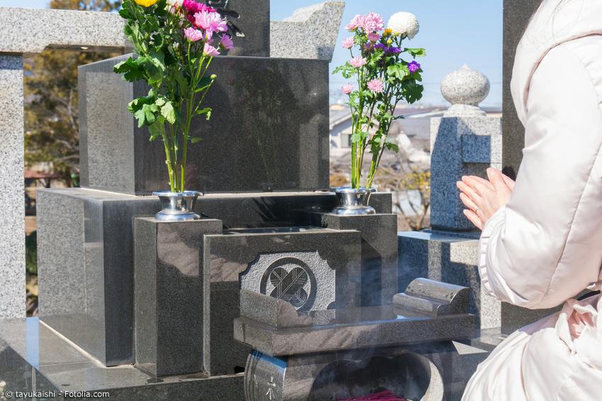Frau betet an japanischem Grab