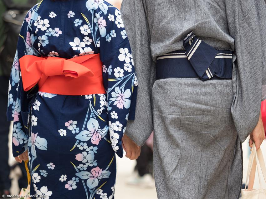 Damen Kimono mit Blüten, daneben schlicht grauer Herren-Kimono