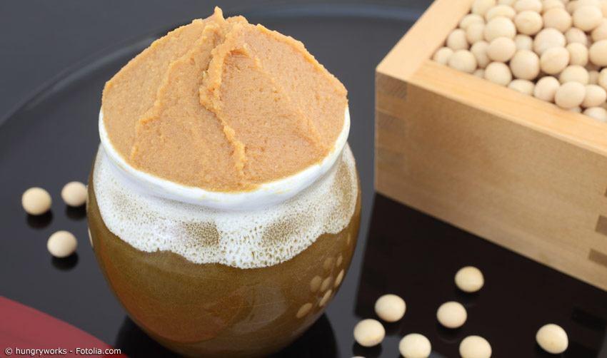Miso-Paste in Gefäß mit getrockneten Sojabohnen im Hintergrund