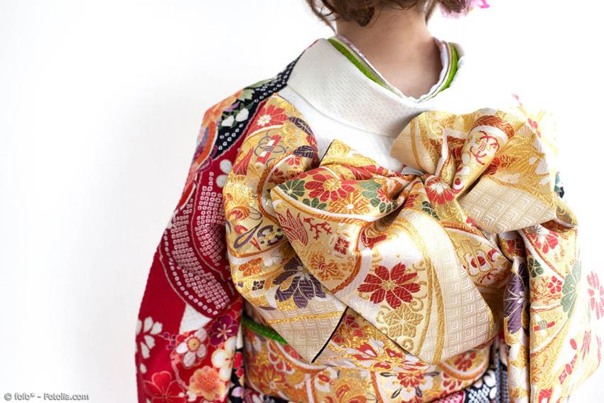 Einen Kimono anzuziehen ist gar nicht so einfach. Deshalb gibt es für besondere Anlässe extra Anziehhilfen, die die Trägerin beim Anlegen der einzelnen Schichten und beim Binden der Obi und Schleife unterstützen.