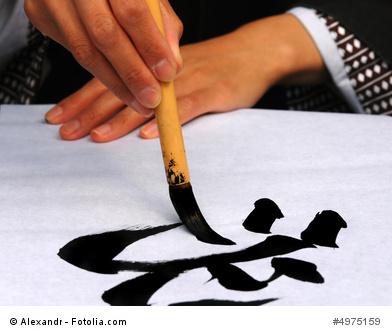 Zeichnen einer japanischen Kanji Kalligraphie mit Pinsel und Tusche