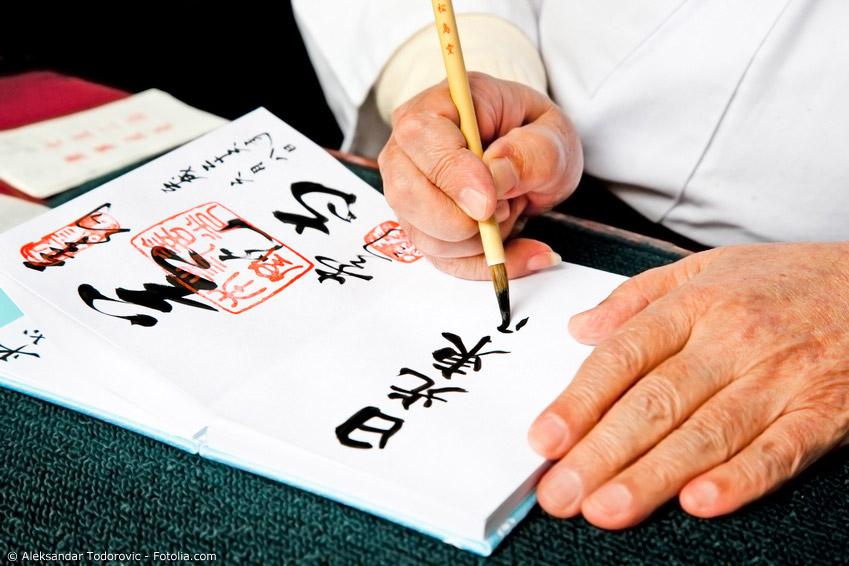 Ein Prieser im Schrein in Nikko schreibt eine Kalligraphie in das Tempelbuch eines Besuchers.