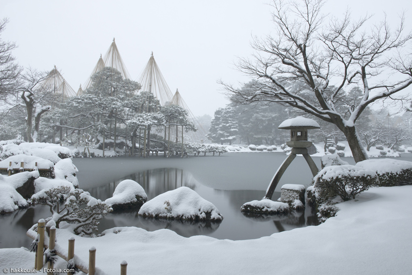 Kenrokuen im Winter mit zugefrorenem Teich und Laterne