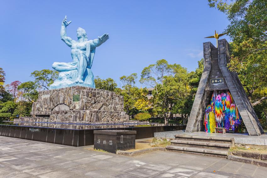 Links im Bild ist das Nagasaki Friedensmonument zu sehen, rechts daneben steht eine Gedenkstatue, in der Girladen aus Kranichen aufgehängt werden