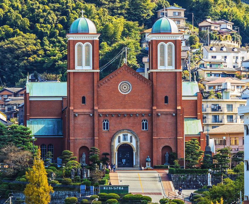Die wiederaufgebaute Urakami-Kathedrale in Nagasaki, im Hintergrund die kaskadierenden Häuser.