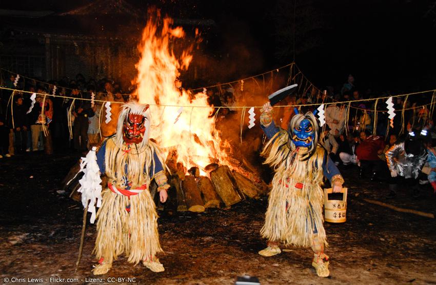 Zwei Namahage vor einem großen Feuer