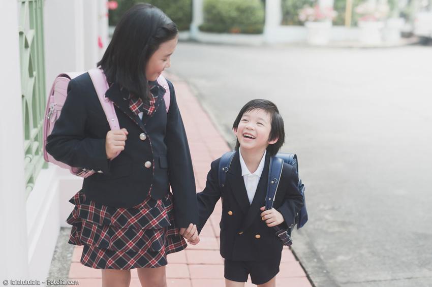 Mädchen mit kleinem Bruder in Schuluniform