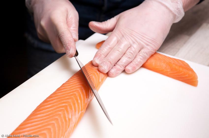 Lachsfilet wird mit einem Japan Messer in gleichgroße Stücke geteilt