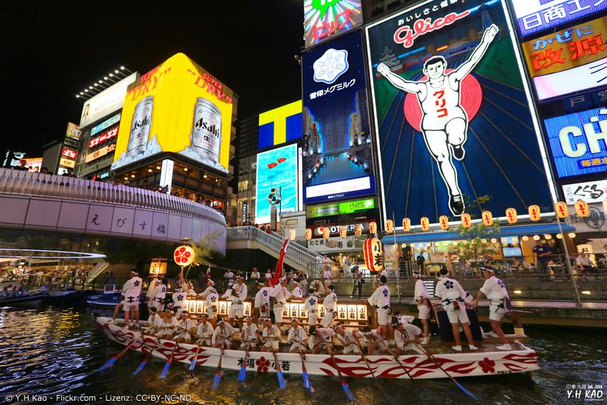 Boot mit Festival-Teilnehmern vor Glico Man in Osaka