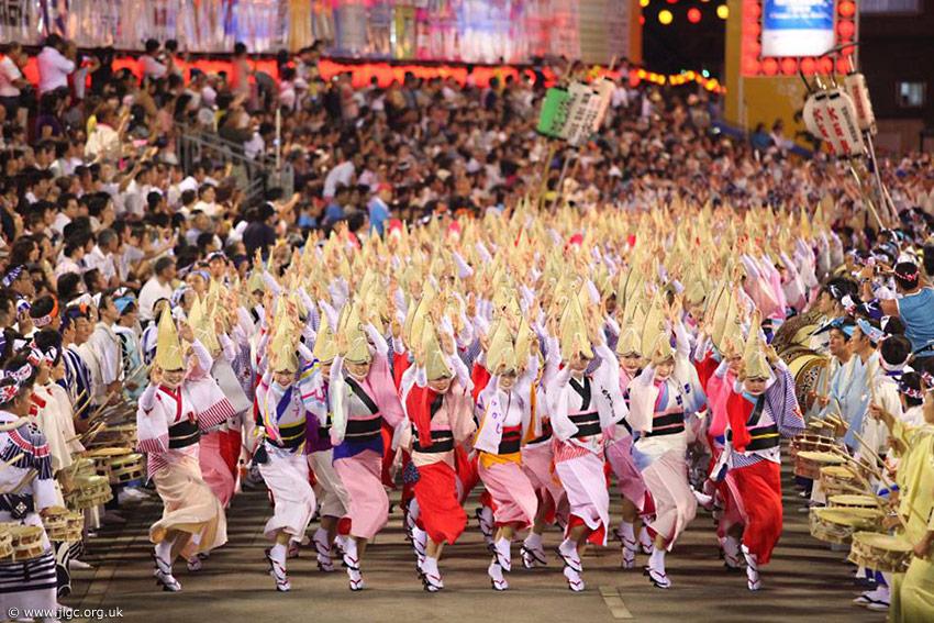 Tanzende Frauen mit typischen Hüten für den Awa Tanz in einer Parade