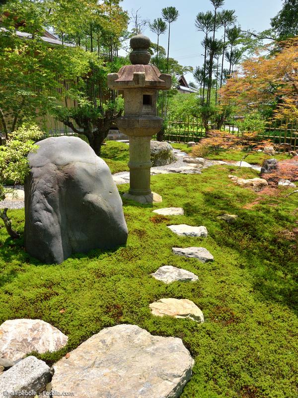 Trittsteine in einer Rasenfläche mit Steinlaterne und Findling
