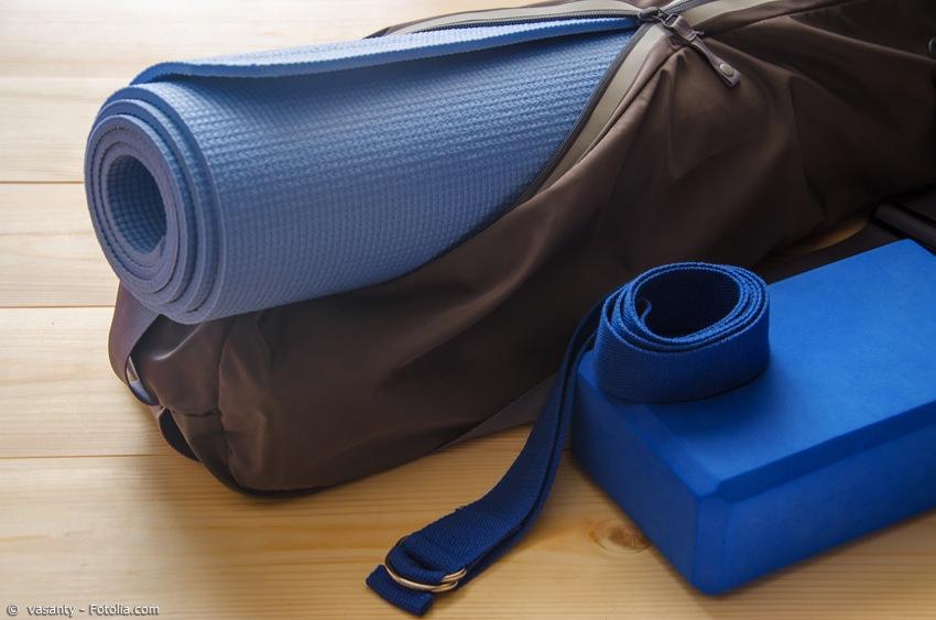 Yogamatte in passender Tasche neben Gurt und Block für Joga