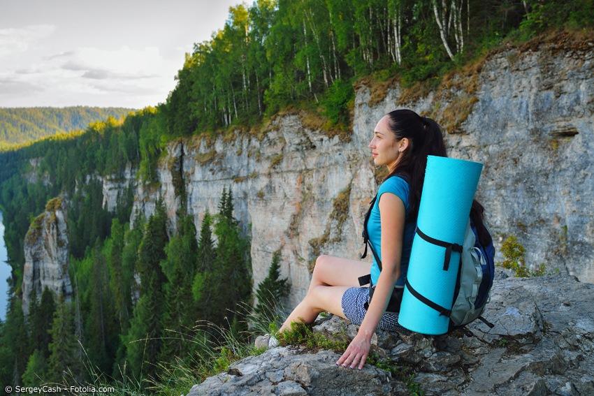 Frau mit Yogamatte vor bergiger Landschaft