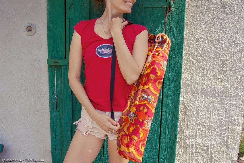 Frau mit Yogatasche über der Schulter bei sonnigem Wetter